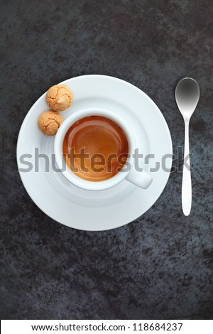 Overhead view of strong frothy espresso coffee in a cup and saucer with two traditional macaroons and a silver teaspoon - stock photo