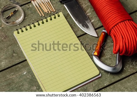 Overhead view of survival gear equipment to survive and Notebook with Pen.Items include knife, red rope, notepad, pen, compass, matches. Writing Notes for Traveller with green wooden background. - stock photo
