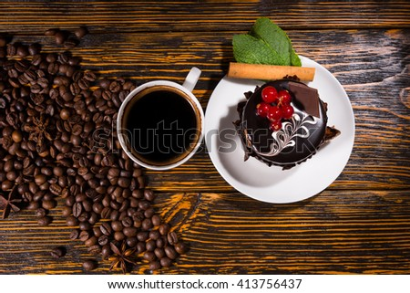 Overhead view of tasty chocolate dessert on white plate by coffee mug and beans spread across wood table - stock photo