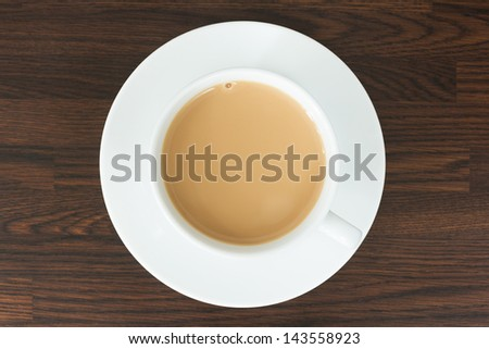 Overhead view of tea in a cup and saucer on a wooden worktop - stock photo