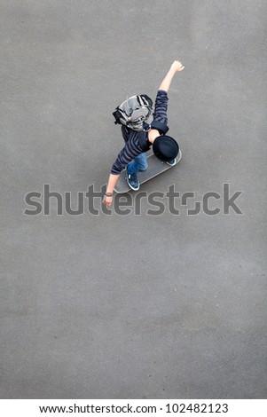 overhead view of teen boy skateboarding - stock photo