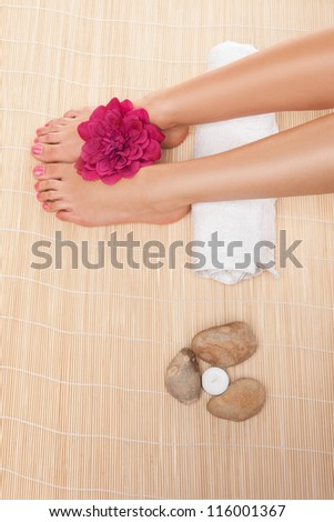 Overhead view of the feet of a woman resting on a rolled white towel with a flower and hot stones while having a spa treatment - stock photo