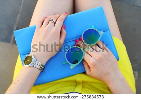 Overhead view of trendy girl accessories blue handbag and green sunglasses . Summer outfit  - stock photo