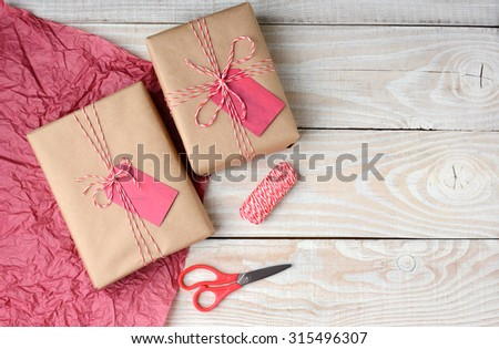 Overhead view of two Christmas presents wrapped in plain brown paper and tied with red and white string, Scissors,, spool of string and red tissue paper with copy space. - stock photo