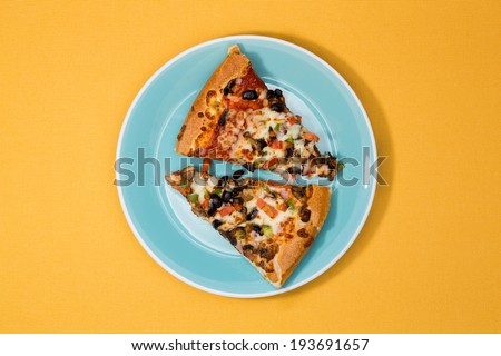 Overhead view of two freshly baked slices of savory pizza with cheese, tomato, olives and herbs on a blue plate over a yellow background - stock photo