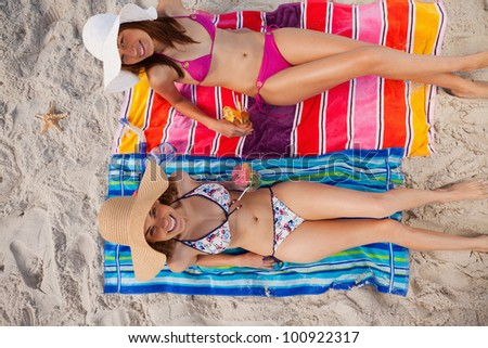 Overhead view of two women looking at the camera with beaming smiles - stock photo
