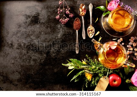 Overhead view of various sorts of tea. Flavoured with Assorted Herbs, an apple, rose with a teapot and a teacup on a rustic black metal board - stock photo