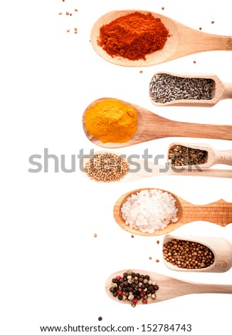 Overhead view of wooden scoops and spoons in different shapes and sizes filled with assorted spices and condiments isolated on white with copyspace - stock photo