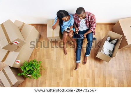 overhead view of young black african couple with moving boxes in new apartment using modern tablet computer technology - stock photo