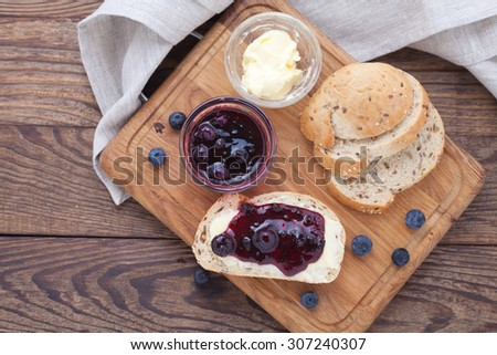 Overhead view on healthy breakfast with strawberry jam. Blueberries and red currants jam, butter and bread on wooden table. Breakfast with fruits top view horizontally. Macro shot selective focus - stock photo