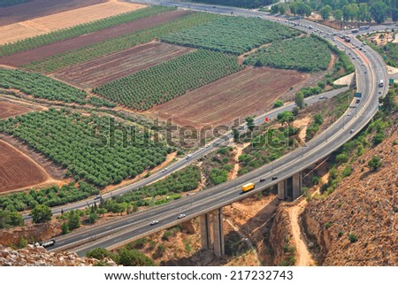 Overhead view on running highway among grain fields and plantations of olive and fruit trees in agriculture valley. Galilee, Israel - stock photo