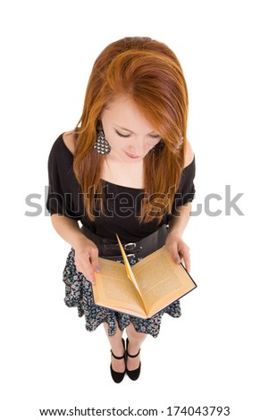 Overhead view, pretty redhead reading a book - stock photo