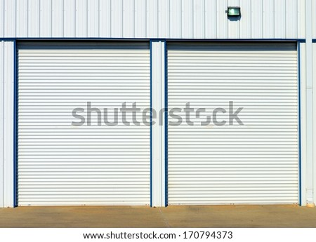 Overhead White Steel Doors At Garage Or Storage Unit With Security Light - stock photo
