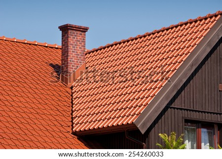 Overlapping red tiles rows sheet roof and chimney, new house building construction of high section in Poland, architecture detail, ridge tiling material regular pattern in horizontal orientation - stock photo