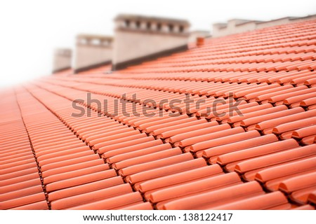 Overlapping rows of red tiles roof with chimneys in Poland, ridge tiling material regular pattern background in horizontal orientation, nobody. - stock photo