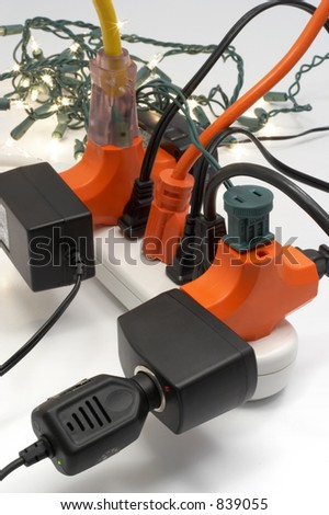 Overloaded electrical power strip with Christmas lights in background - stock photo