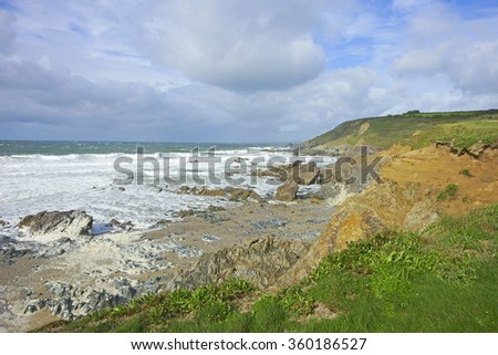 Overlooking the beach at Gunwalloe Church Cove on a very stormy day with an incoming tide, messy surf and sea foam/froth blown across the beach, The Lizard Peninsula, Cornwall, United Kimgdom - stock photo
