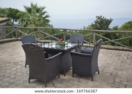 Overlooking the italian ocean with roses on the table - stock photo