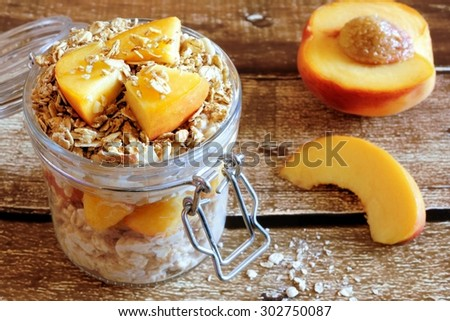 Overnight oats with fresh peaches and granola in snap lid glass jar on rustic wood - stock photo