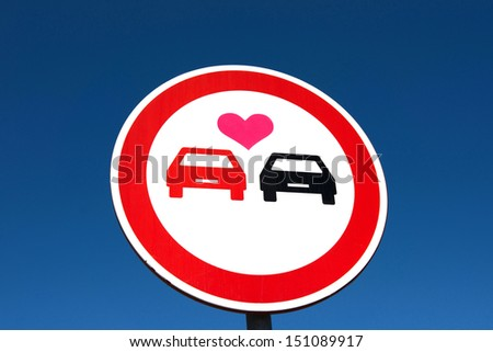 Overtaking sign with a love heart between the cars. Car lover - stock photo