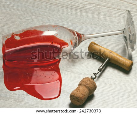 overturned glass with spilled wine and a corkscrew with cork.toned - stock photo