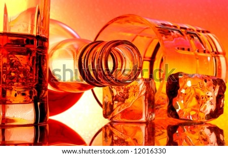 Overturned whiskey bottle and glasses in front of multi colored abstract background. - stock photo