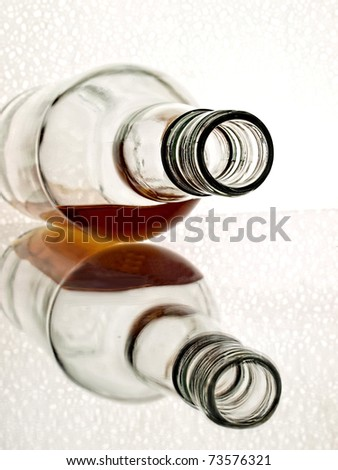 Overturned whiskey bottle with reflection on white background. - stock photo