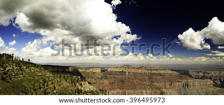 Overview of red rock canyon, deep blue sky white fluffy clouds, green brush and tress on mountain top. - stock photo