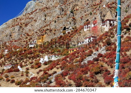 Overview of the mountain slope-caves-buildings-prayer flags on way down from the main edifices of Drak Yerpa monastery-complex of + than 80 buddhist meditation caves at 4885 ms.alt. Lhasa pref.-Tibet. - stock photo