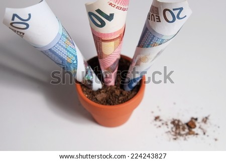 Overview of three Euro banknotes planted in a clay pot growing out. Isolated objects with debris on the table surface - stock photo