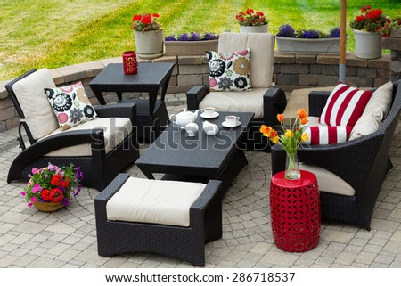 Overview of Upscale Patio Set, Dark Wicker Luxury Furniture with Comfortable Cushions on Outdoor Stone Patio of Affluent Home - stock photo