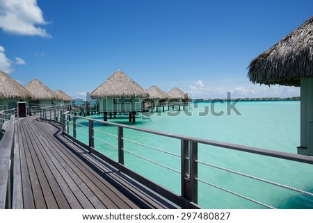 overwater bungalows with a thatched roofs in a honeymoon vacation resort in the clear blue lagoon on the tropical island of Bora Bora, near Tahiti, in French Polynesia. - stock photo