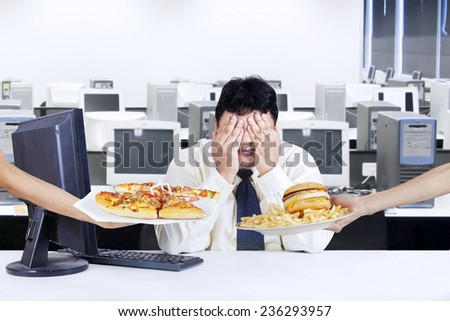 Overweight businessman try to healthy life and avoid a temptation of fast food - stock photo
