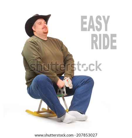 Overweight cowboy riding on a rocking horse. Picture with space for your text. - stock photo