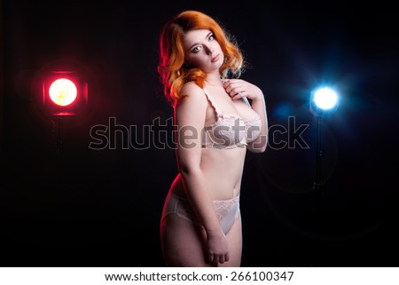 Overweight girl in underwear on black background. Cute glamour with a blue and red light behind her. Shot in studio on black background - stock photo