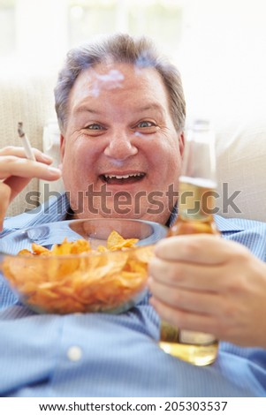 Overweight Man Eating Chips, Drinking Beer And Smoking - stock photo
