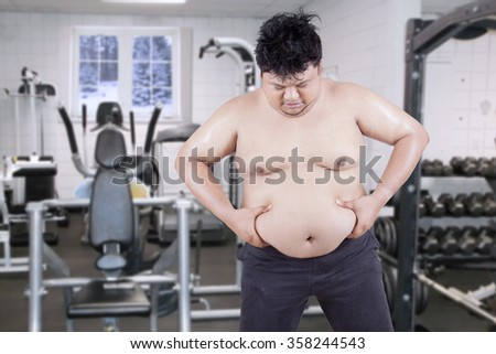 Overweight man grabbing his fat on the stomach. Shot in fitness center - stock photo