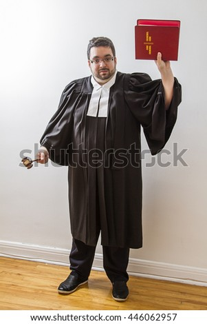 Overweight man in canadian lawyer toga, holding a gavel in his hand and a red bilingual criminal law book in the other - stock photo