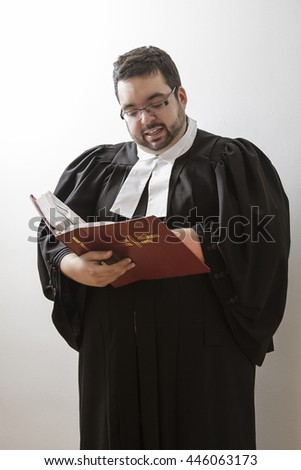 Overweight man in canadian lawyer toga, holding a red bilingual criminal law book and reading in it - stock photo