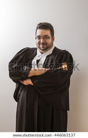 Overweight man in canadian lawyer toga, with a smile and arms cross, holding a gavel in his hand - stock photo