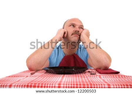 Overweight man looking very unhappy with empty plate in front of him - stock photo