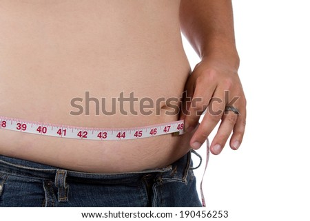 Overweight man measures his waist size. - stock photo