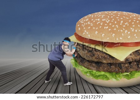 Overweight man pushing a big burger for healthy life - stock photo