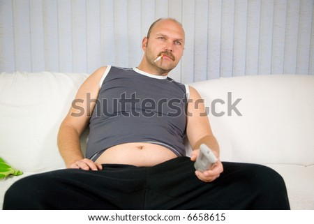 Overweight man sitting on the couch with cigarette in his mouth - stock photo