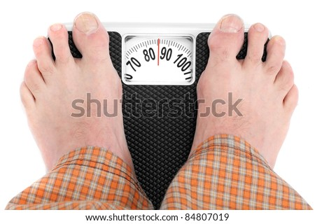 Overweight man standing on a retro style weighing machine isolated on a white background. - stock photo