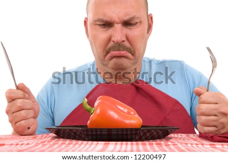 Overweight man with healthy vegetable on plate looking unhappy (focus on pepper) - stock photo