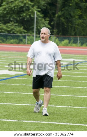 overweight middle age senior man exercising on sports field - stock photo