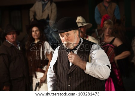 Overweight 1800s style man in front of bandit gang - stock photo