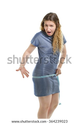 Overweight unhappy young woman measuring her belly over white background - stock photo