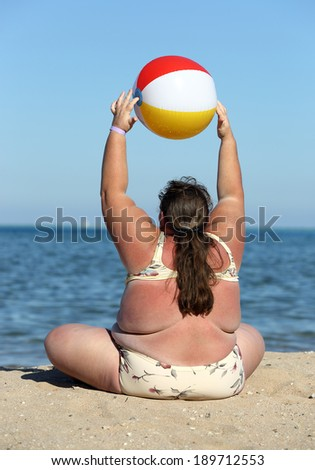 overweight woman doing gymnastics with ball on beach  - stock photo